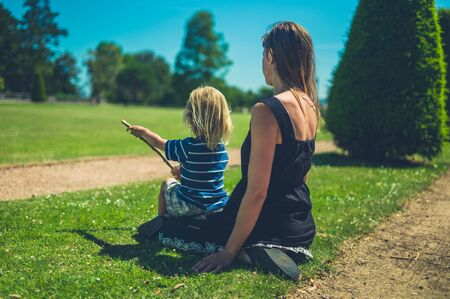 A young mother and her toddler are relaxng in the park on a sunny summer day Stockfoto