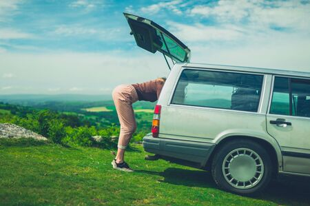 A young woman is looking for something in the trunk of her car in nature on a sunny summer day Stockfoto