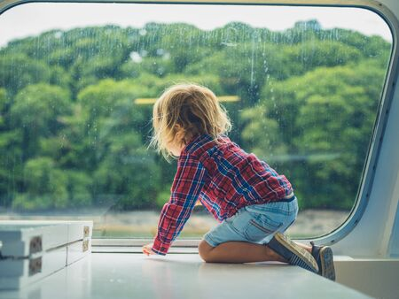 A little toddler is sitting by the window of a passenger ferry