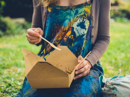 A young woman is enjoying a picnic in the park Stockfoto