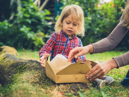 A little toddler is enjoying a picnic in the park with his mother