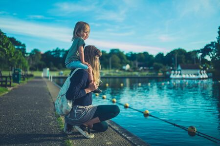 A little toddler is sitting on his mothers shoulders by a lake in a park at sunset