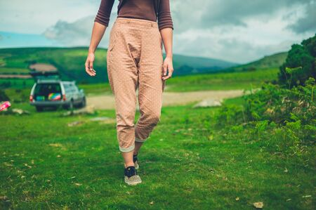 A young woman is walking in nature after parking her car Stockfoto