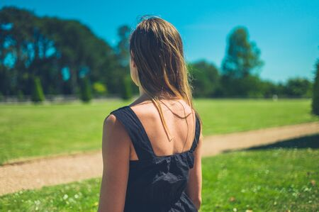 A young woman is standing in the park on a sunny summer day Stockfoto