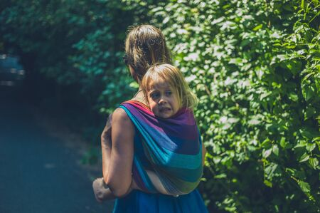 A young mother is carrying a big toddler in a sling on her back
