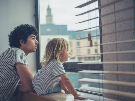 A young father and his toddler are looking out the window of a city apartment Zdjęcie Seryjne