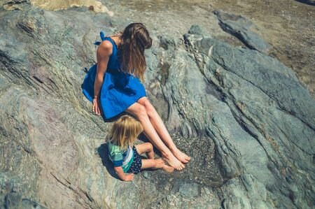 A young mother and her toddler are sitting on some rocks in the summer Zdjęcie Seryjne