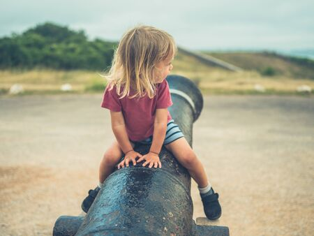 A little toddler is sitting on a canon outdoors on a summer day