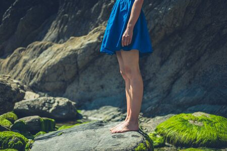 A young woman is standing on a rocky beach in the summer