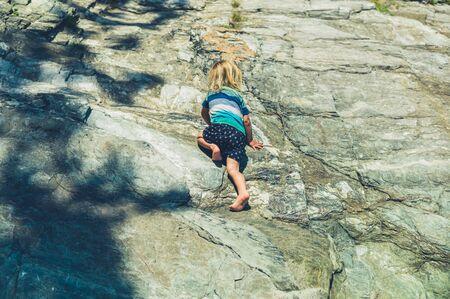 Un petit enfant grimpe sur des rochers en été