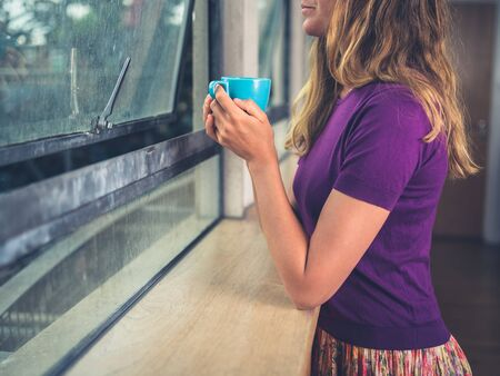 A young woman is drinking coffee by the window in a city apartment Zdjęcie Seryjne