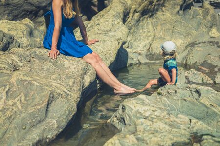 A young mother and her toddler are relaxing by a rockpool on the beach in summer