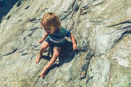 A little toddler is climbing on some rocks in the summer