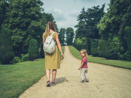 A young mother and her toddler are standing on a path in a park