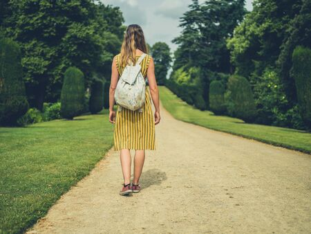 A young woman is walking on a path in a park