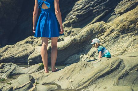 A young mother and her little toddler are walking on a rocky beach in the summer