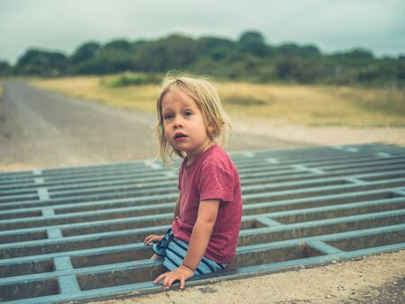 A little toddler is playing on a cattle grid