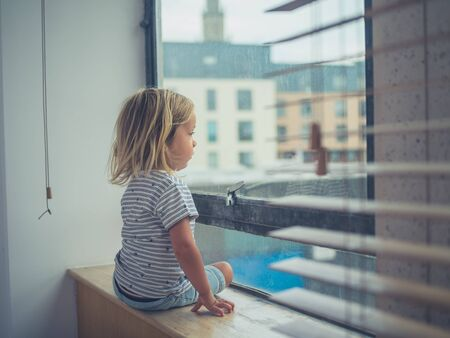 A little toddler is sitting by the window of a city apartment