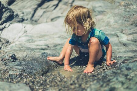 A little toddler is playing with the water on a rocky beach