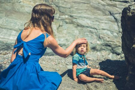 A young mother is on the beach with her toddler and is applying suncream to his skin