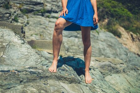 A young woman wearing a blue dress is standing on some rocks in the summer Zdjęcie Seryjne