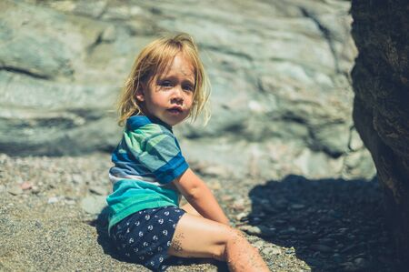 A little toddler is sitting on the beach with suncream on his face Zdjęcie Seryjne