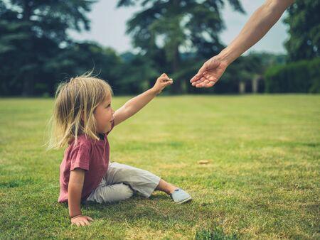 Ein kleines Kleinkind sitzt auf der Wiese in einem Park und bietet seiner Mutter eine Blume an