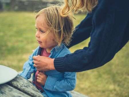 A young mother is helping her toddler with his shirt buttons outside at picnic table