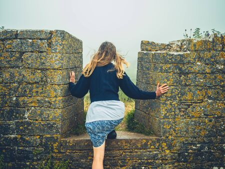 A young woman is climbing a historic wall in the mist