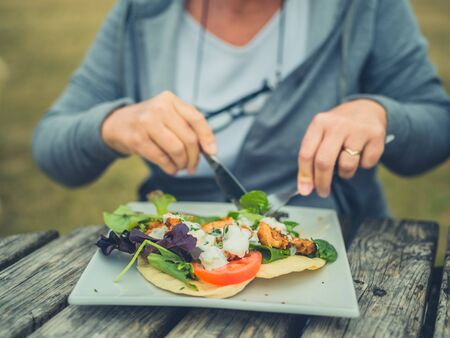 A senior woman is eating salad and a wrap for lunch at a picnic table outdoors