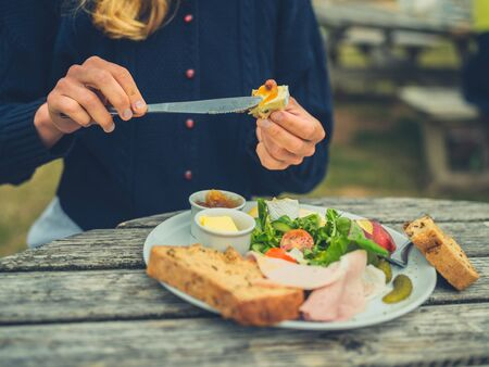 A young woman is buttering bread outdoors at a picnic table to make a sandwich
