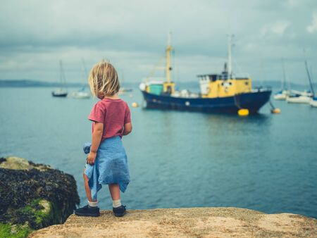 A little toddler is walking in a harbor on a summer day
