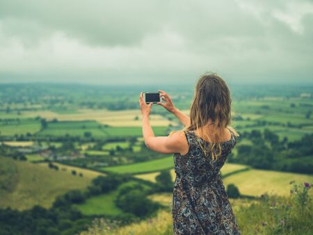 A young millennial woman is using her smartphone to take photos in nature on a foggy day Stockfoto