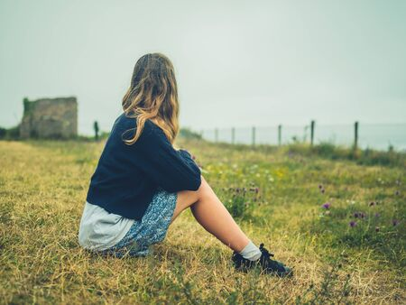 A young woman is sitting and resting on the grass by the seaside on a foggy day Stockfoto