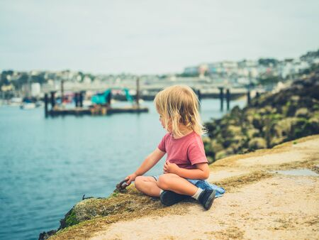 A little toddler is sitting in the harbor on a summer day Stockfoto