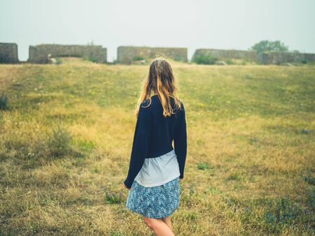 A young woman is standing in a historic field with ruins in the mist Stockfoto
