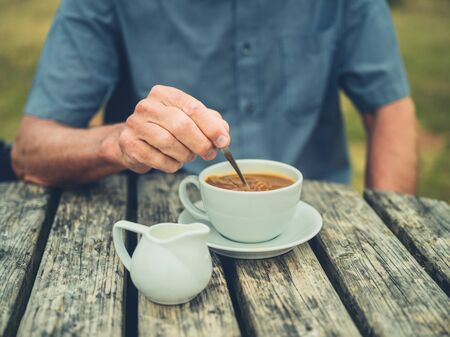 A senior man is drinking coffee with milk outdoors at a picnic table Stockfoto
