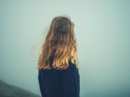 A young woman is standing in the mist