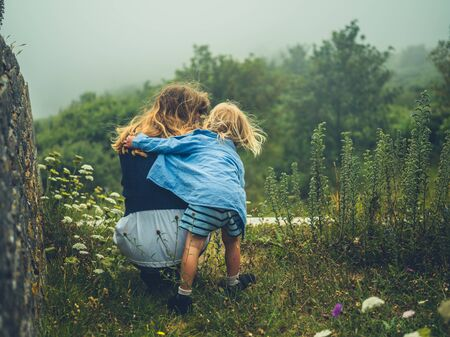 A little toddler is embracing his mother in nature on a misty day Stockfoto