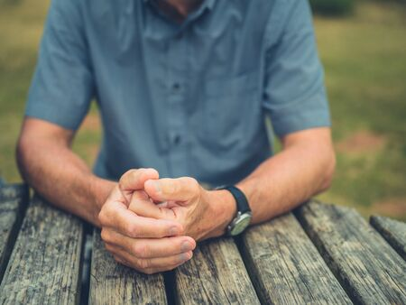 A senior man is resting his hands on a table outdoors