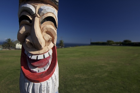Tiki totem pole caricature against blue sky and green grass Stock fotó