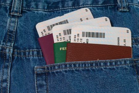 Horizontal orientation of the passports photo differents countries and plane tickets in blue jeans back pocket photo
