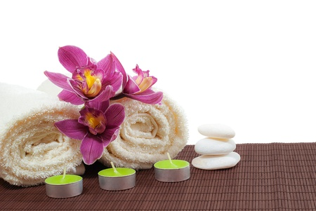 A beautiful orchids roses, soft cotton towels and green candles on bamboo background photo