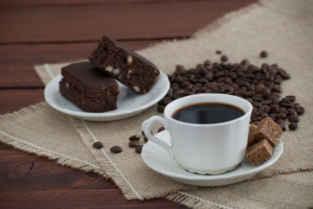 dark coffee with brown sugar cubes, the bottom plate of chocolate brownies on the wooden table decorated with burlap coffee beans photo