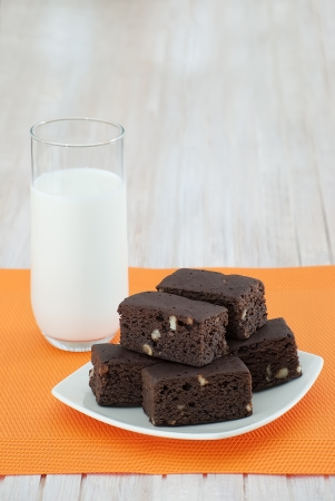 Tower of homemade chocolate brownies and a glass of milk on tablecloth orange, on a white wooden table photo