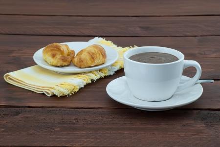 tazza di cioccolato caldo con due croassants sulla piastra su tovagliolo giallo su tavola di legno