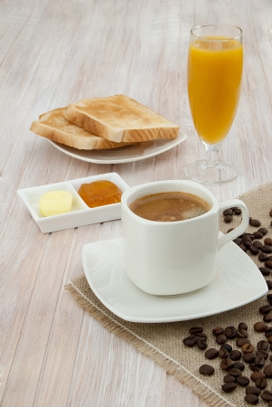 Breakfast with coffee, toast with jam and butter and orange juice on wooden table decorated with white cloth jute coffee beans photo