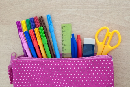 Assorted school supplies in case on wooden desk photo