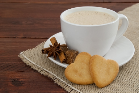 Cream coffee with cookie hearts decorated with cinnamon and star anise and brown sugar lumps on burlap