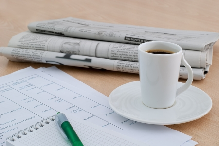 taking a coffee at the office desk with the morning newspaper background photo